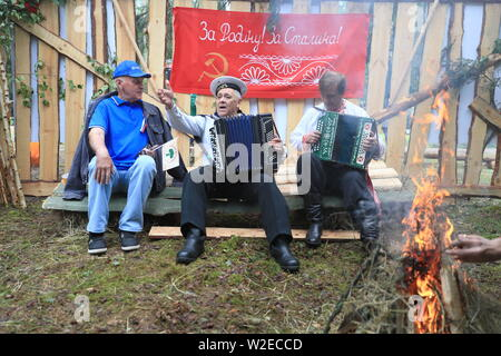 Russia. 07th July, 2019. PSKOV REGION, RUSSIA - JULY 7, 2019: Men play accordeons by a bonfire during the 60th Kurgan Druzhby meeting attended by Soviet Army veterans and guerrillas who fought against Nazi Germany during the Great Patriotic War (part of WWII) in 1941-1945 and who now live in Russia, Belarus and Latvia. Vladimir Smirnov/TASS Credit: ITAR-TASS News Agency/Alamy Live News - Stock Photo