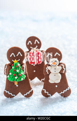 Gingerbread cookie men with tiny marzipan snowman - Stock Photo