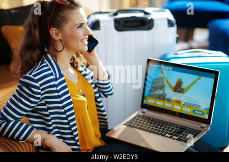 Smiling elegant solo traveller woman in striped jacket sitting near couch and trolley bags at modern home booking airplane tickets online an a laptop - Stock Photo