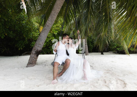Newlyweds kiss on a swing under a big palm tree. Wedding on a tropical island. - Stock Photo