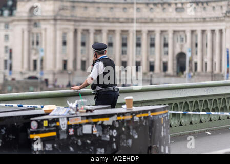 Police officer checking the damage to Westminster Bridge after it was hit by a City Cruiser vessel. Westminster, London, UK. Incident tape. Space copy - Stock Photo