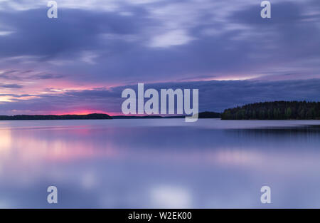 Long exposure sunset above one of the many lakes in Finland - Stock Photo