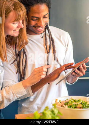 Interracial couple formed by African and Caucasian prepare a salad together with the help of their cell phone - Stock Photo