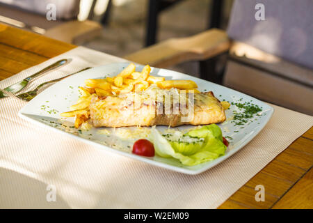 Traditional Montenegrin Meat Negush Steak on a white plate in a restaurant. - Stock Photo