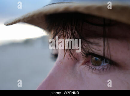 A look in the direction of a brunette with brown eyes with a bang in a straw hat - Stock Photo