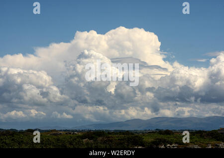 These clouds towering over the moumtains of North Wales. They often result in thunder storms and heavy rain - Stock Photo