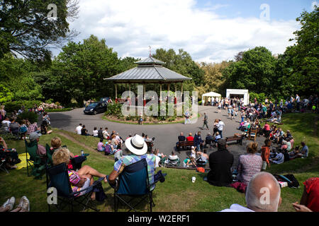 Residents of Huddersfield, West Yorkshire UK congregate in Beaumont Park on a sunny summer weekend to picnic and enjoy entertainment at the bandstand - Stock Photo