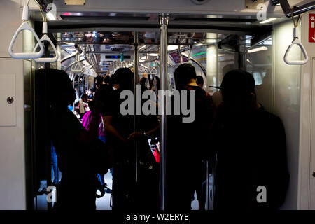 Passengers in Singapore Mass Rapid Transit (MRT) train. The MRT has 102 stations and is the second-oldest metro system in Southeast Asia - Stock Photo