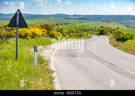 Beautiful landscape, spring nature. Winding provincial road among sunny fields in Tuscany, Italy - Stock Photo
