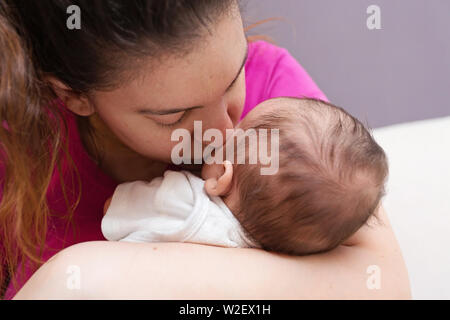 Loving Mom snuggling and kissing her brand new baby - Stock Photo