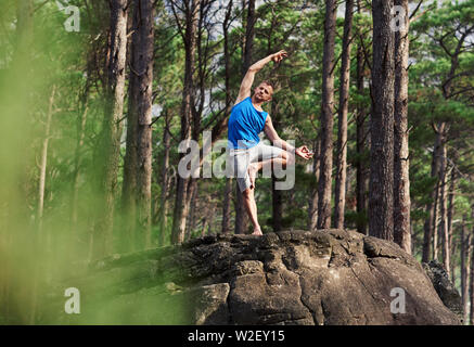 Fit man doing the bending tree pose in a forest - Stock Photo