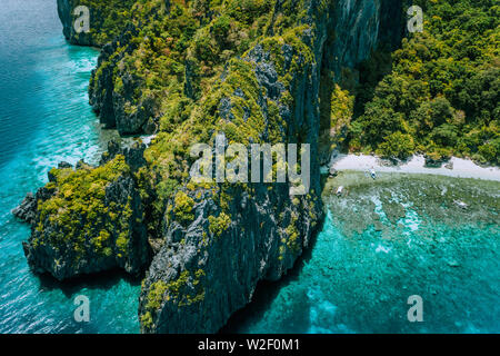 Aerial drone view of tropical island Entalula El Nido Palawan, Bacuit archipelago Philippines. Karst limestone rocky mountains surrounds blue bay with - Stock Photo