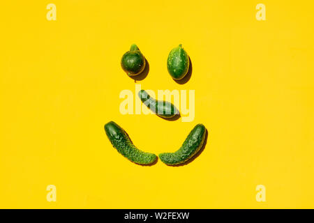 Different sizes and forms cucumbers on a yellow background forms a smiling face. Smile, face, emoji, smiley, happy smiley, happy emoji, smiling emoji. - Stock Photo