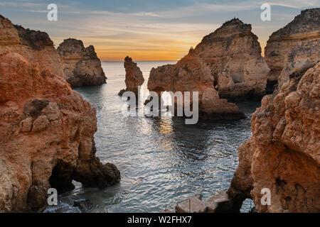Amazing landscape at sunrise. Beautiful beach near Lagos in Ponta da Piedade, Algarve region, Portugal.  Seascape with Cciff rocks. - Stock Photo