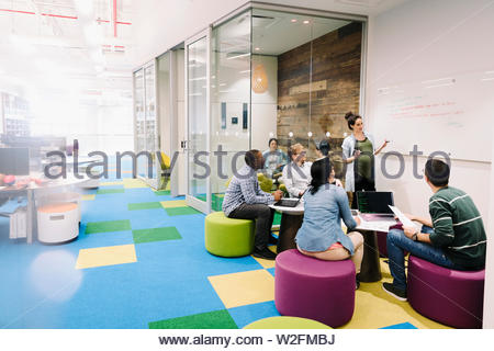 Compute programmers meeting in creative open plan office - Stock Photo