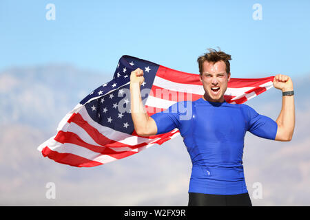 American success man athlete winning with USA flag celebrating victory. Fit male winner fitness model cheering in celebration of success win. Face expression with determination. - Stock Photo