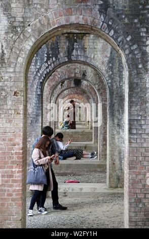 Japanese youg couples relaxing under Suirokaku brick aqueduct, Nanzenji temple, Kyoto, Japan - Stock Photo