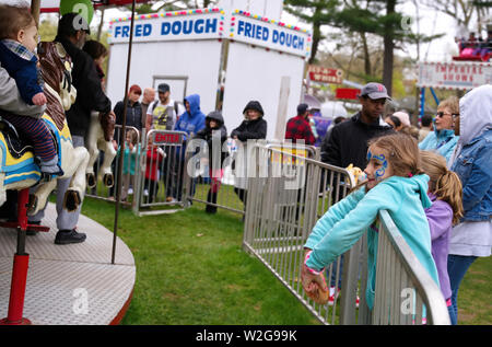 Meriden, CT USA. Apr 2019. Daffodil Festival. Young girl with face art waiting for her time on the merry go round. - Stock Photo