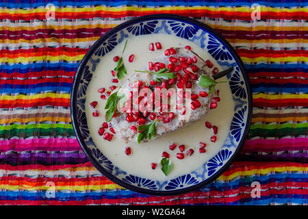 Mexican Cuisine, traditional Chile En Nogada on talavera dish from Puebla on Mexican colors - Stock Photo