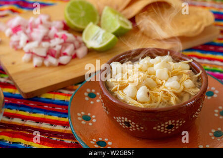 Mexican cuisine, chicken pozole served with radishes, lemons and toast, chile de árbol and oregano with a colorful Mexican background. - Stock Photo