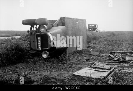 Traffic accident with tilted passenger car on the roadside ca. 1930 - Stock Photo