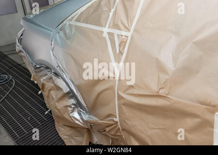 A large silver sedan car is completely covered in paper and adhesive tape to protect against splash during painting after an accident in a workshop fo - Stock Photo