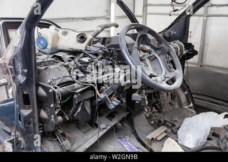 Car interior in the back of a van with a disassembled dashboard and view on steering wheel during preparation in a vehicle repair workshop. Auto servi - Stock Photo
