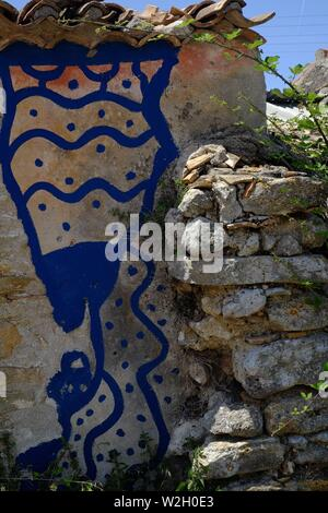 Blue painted graffiti on a section of wall attached to a new house in the hillside village of AFionis in Corfu* - Stock Photo