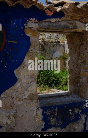 Blue painted graffiti on a wall attached to a newhouse in the hillside village of Afionis in Corfu - Stock Photo