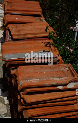 Rustic orange/brown roof tiles situated in a narrow street in the hillside village of Afionis in Corfu - Stock Photo