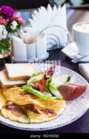Omelet with vegetables, bacon on plate. Summer dish with omelette, greens and sausage. Snack in cafe - Stock Photo