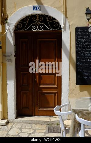 Brown panelled door in archway in shade in Corfu town small square panels and intricate design above door made from oak - Stock Photo