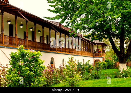 old style rustic house with laborious wood porch and front green garden tree - Stock Photo