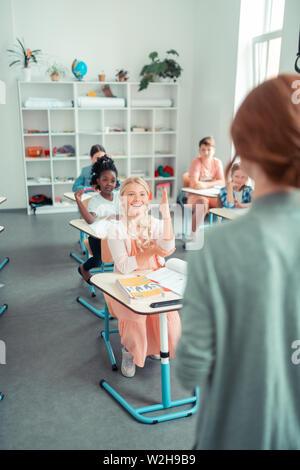 School children raising hands during the lesson. - Stock Photo
