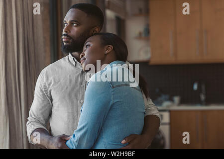 African American couple hugging and looking out of their window - Stock Photo