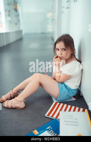 Girl sitting on floor near lockers after fight with classmates - Stock Photo