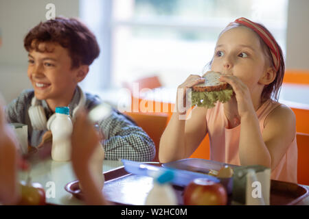 Girl making funny face while eating yummy sandwich - Stock Photo