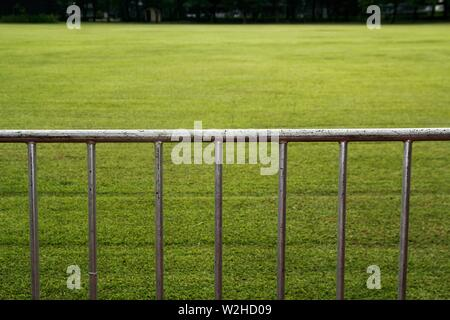 Photo of a steel fence or barricade and a green grass field - Stock Photo
