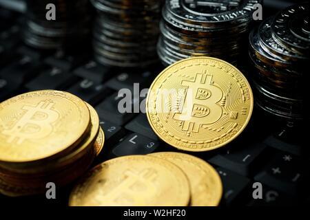 Bitcoins on a keyboard computer. - Stock Photo