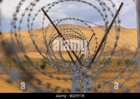 Barbed wire drawn in circles against a background of mountains - Stock Photo