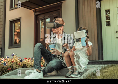 Modern blonde father sitting on the porch with his daughter