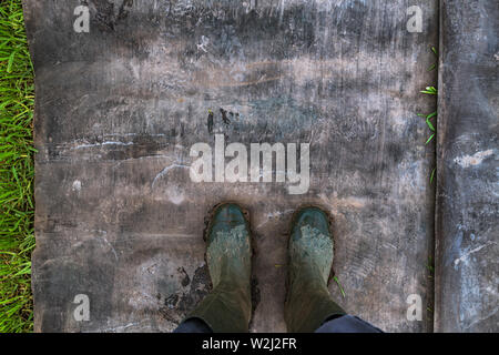 Top view of farmer wearing dirty rubber boots after walking through muddy field - Stock Photo