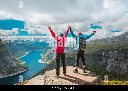 Couple posing on Trolltunga. Happy woman and man enjoy beautiful lake and good weather in Norway. - Stock Photo
