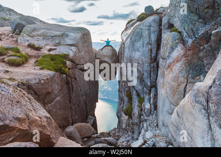 Woman on Kjeragbolten Travel in Norway Kjerag mountains, extreme vacations, adventure, tourist, happy emotions, success concept - Stock Photo