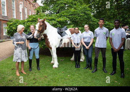 The Duchess of Cornwall meets with Laura Boland yard manager and young people who have taken part in programs with the charity and Splash one of the Brixton based Ebony Horse club charity horses during a reception for Ebony Horse Club at Clarence House in London. - Stock Photo