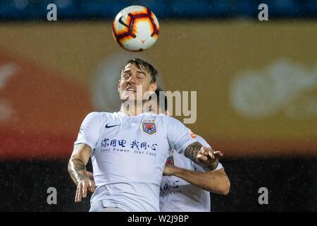 Brazilian football player Roger Krug Guedes, known as Roger Guedes, top, of Shandong Luneng Taishan heads the ball against Beijing Renhe in their 16th round match during the 2019 Chinese Football Association Super League (CSL) in Beijing, China, 7 July 2019. Shandong Luneng Taishan defeated Beijing Renhe 2-0. - Stock Photo