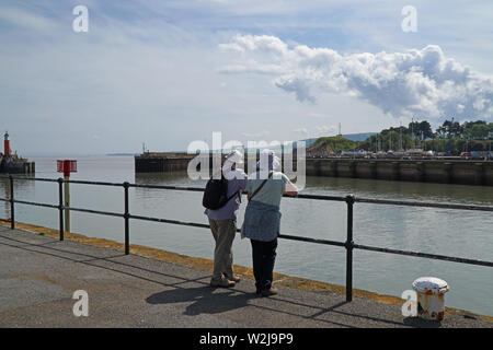 A rear view of a mature couple looking out to sea from a small harbour on a sunny day - Stock Photo