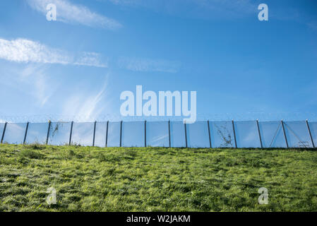 Security fence topped with razor wire. - Stock Photo