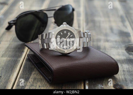 Still life men's accessories with  watch, leather wallet, and sunglasses on old grunge wooden table. Set of men's accessories for the business. The co - Stock Photo