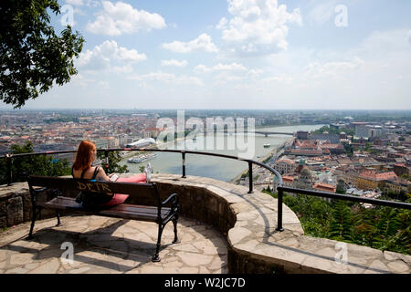 A woman sits on a bench alone nbjoying the view over Budapest from Gellert Hill - Stock Photo